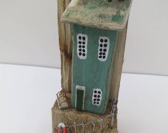 Green driftwood cottage on split driftwood block
