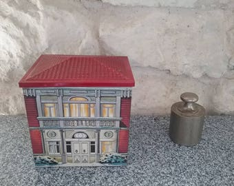 Vintage metal house shaped box. House in winter, snow