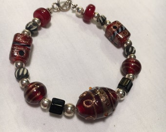Burgundy and silver multi-size beaded bracelet on with with silver clasp