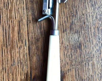 Vintage peeler, made of stainless steel, with a bakelite handle, brand FAMOS, from the sixties