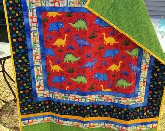 Dinosaur baby quilt bright colors, hand made, measures 34 x 42 in.