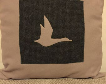 Cushion with flying duck sillhouette