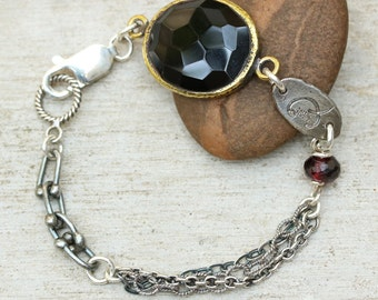 Oval faceted onyx bracelet in brass bezel setting with garnet beads secondary gemstone and oxidized sterling silver triple chain
