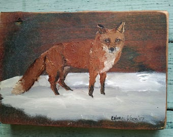 Red fox in snow on wood
