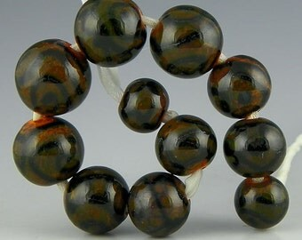 a set of 11 graduated rounds in dark brown with black patterning handmade lampwork glass beads - Revolutions