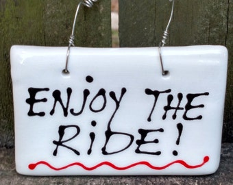 Enjoy the ride. Hanging sign.