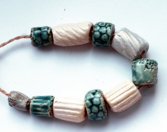 Oceans of unthinking night -- a set of 10 antique-looking iridescent, satin white and turquoise ceramic  beads
