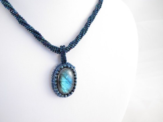 Necklace, Labradorite cab bead embroidered with blue seed beads hung on a twisted herringbone rope with a pewter heart clasp