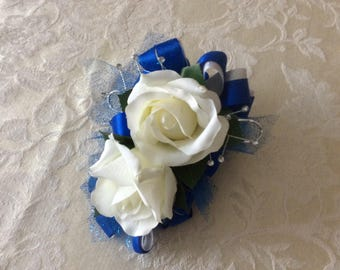 Corsage and matching boutonniere in white roses and royal blue ribbon