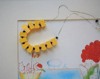 Yellow plastic cubes and Pearl Necklace in black glass