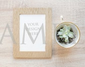 Rose gold blank frame simple mockup with teacup and succulent on wood stock photo - vertical