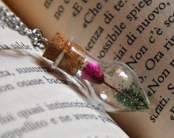 Pendant nature, with fuchsia flower in a glass bottle shaped ampoule and glitter in green
