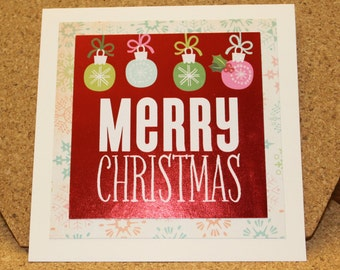 Merry Christmas card - shimmery ornaments on snowflake mat