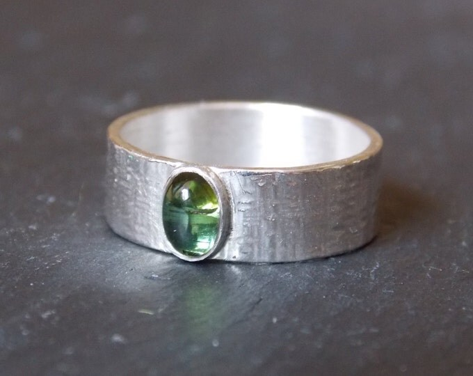 With stone studded silver ring. Ring hammered silver with a set with green tourmaline stone.