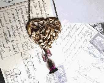 Art Nouveau necklace gold plated (?) heart shaped with openwork plant motifs and culture and purple glass beads
