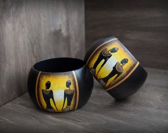 Wooden bracelet with a painted african women. Gold, brown, yellow.