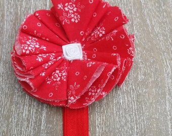 red baby headband with rd and white fabric flower rosette and white flower insert.
