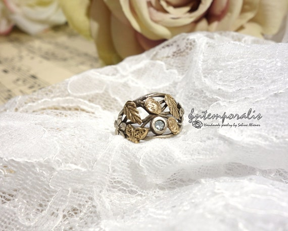 White bronze, silver color, ring decorated with gold bronze flowers and leaves and light blue cubic zirconium, french size 55, OOAK, SABA16