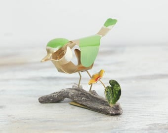 Vintage Brass Bird w/ Green enamel paint and yellow flower on a ceramic branch.