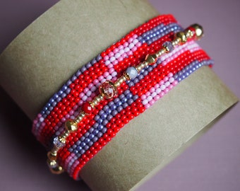 ombre rug design peyote seed bead bracelet with a golden strand of beads and crystals. pink, purple, red ombre double strand cuff bracelet.