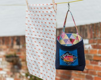 Peg bag with a foxy patchwork block detail to the front, a colourful lining and a single handle and attached washing line clasp