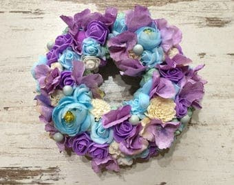 Artifical flower wreath in the shades of blue and purple