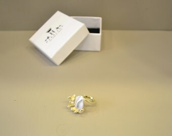 Particularly at flower ring in silver with gold pearl