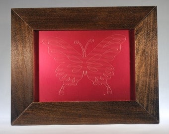 Buttlerfly etched on rose-colored tin and a frame