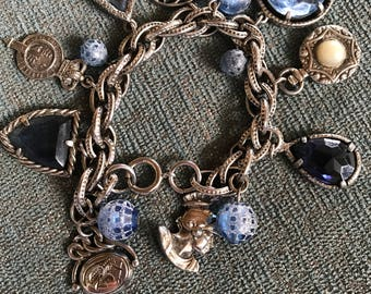 Silver charm bracelet with blue stones and charms