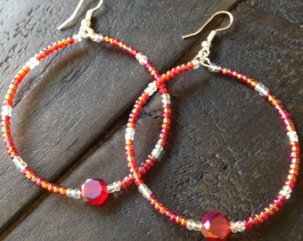 Red  shimmery hoops with red multifaceted center glass bead