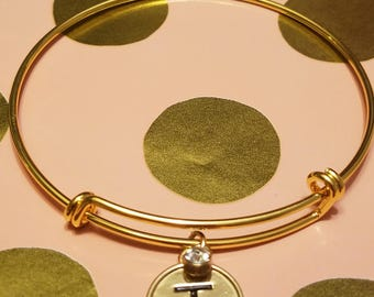 Gold expandable bracelet with gold charm