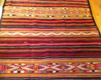 Multicolor striped Kilim rug black Woven wool hands, contemporary background.