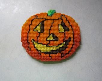 Halloween pumpkin Jack O Lantern made of plastic canvas and yarn with magnets glued to backside
