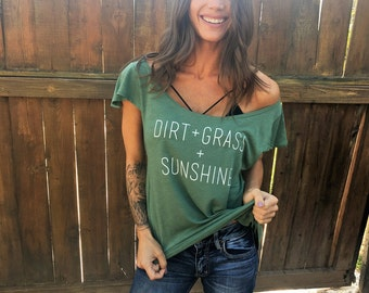 Dirt + Grass + Sunshine. Off the Shoulder Flutter Sleeve Flowy Muscle Tee. Made in the USA. Sizes S-XL.  Off the Shoulder Lounge Tee.
