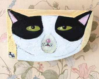 Shaped painting on reclaimed wood of a black and white cat face.