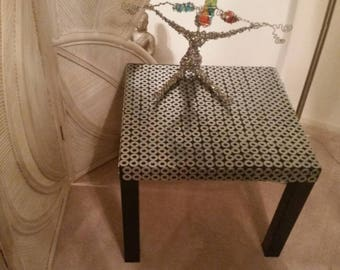 A sofa side table.  An interesting object of Art