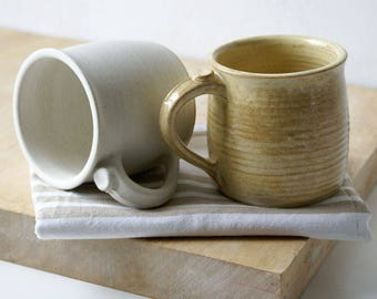 Two tankard style stoneware pottery tea mugs - glazed in pepper yellow and vanilla cream