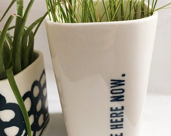 medium porcelain planter screen printed be here now blue text.