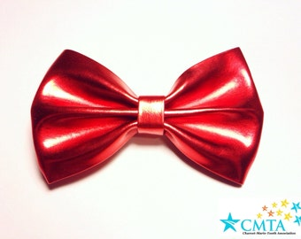 One candy apple red faux leather hair bow. Portion of sale goes to charity. Cruelty-free.