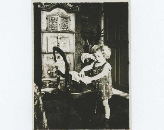 Vintage Snapshot Photo: Small Girl Playing Next to Ornate Stove (612530)