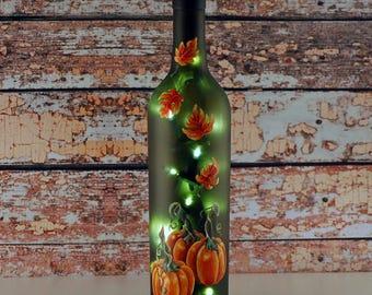 Wine bottle light, hand painted orange pumpkins and autumn leaves