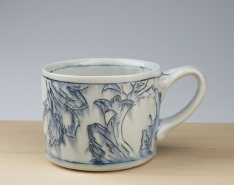 Handmade thrown porcelain mug with toile pattern with ornate handle