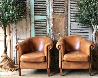 Matching pair of vintage French leather tub chairs
