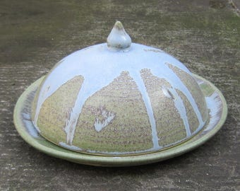 Handmade ceramic cheese plate with rounded cover with semi-matt variegated green and blue glaze