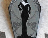 Morticia Addams pin. Coffin shape wooden brooch with own illustration. Morticia from the Charles Addams cartoons. Art deco style image..