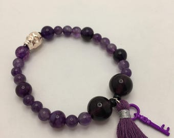 Amethyst Purple Glass Beaded flexible bracelet with a Rose Gold Skull, Purple Tassel, and Purple Skeleton Key.