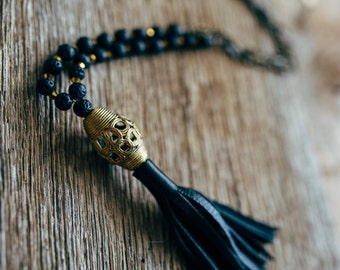 Black Leather Tassel made with Lava Rock Stone Beads, Bronze Oval Link Chain, and an African Trade Brass Bead on Pendant
