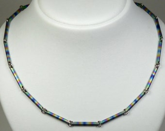 Anodized titanium, steel rings necklace. Rainbow colours anodized titanium, steel rings necklace with toggle clasp.