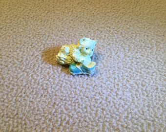 """1/12 """" scale Tan Kitty playing with blue tennis shoe."""