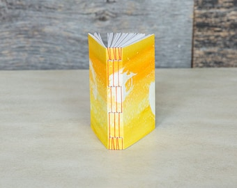 Pocket-sized notebook with yellow watercolor wash and orange stitching